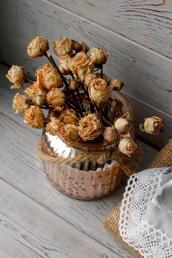 Bloemensamenstelling van roze gedrukte rozen in een bronsvaas die zich op een houten raad bevinden Stilleven bloemensamenstelling royalty-vrije stock afbeelding