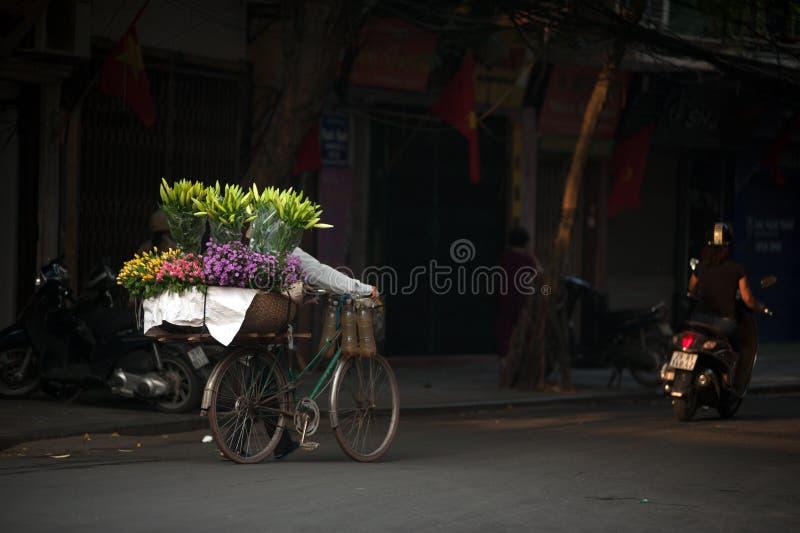 Bloemenstraatventer bij de stad van Hanoi, Vietnam stock afbeelding