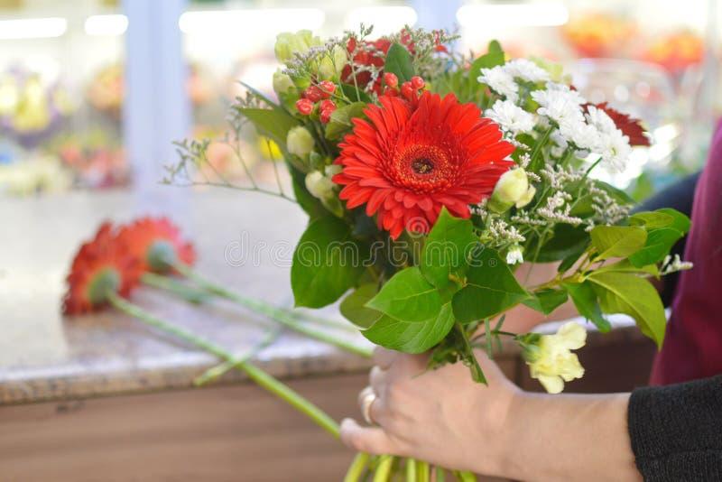 Bloemist aan het werk in de bloemwinkel stock afbeeldingen