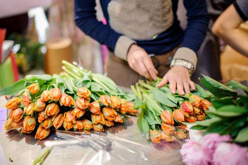 Bloemist die een boeket van oranje tulpen maken royalty-vrije stock fotografie