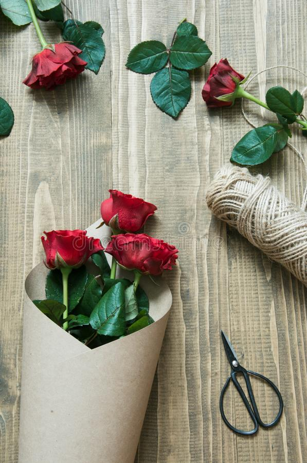 Bloemist die een rood rozenboeket maken, die in kraftpapier-document op een houten lijst verpakken Mening van hierboven royalty-vrije stock foto's