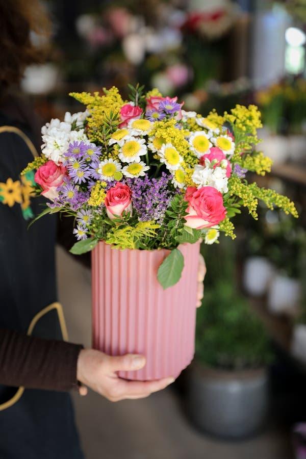 Bloemist die een vaas met mooi bloemstuk van roze rozen, lilac asters, witte chrysanten en andere installaties in houden royalty-vrije stock afbeelding
