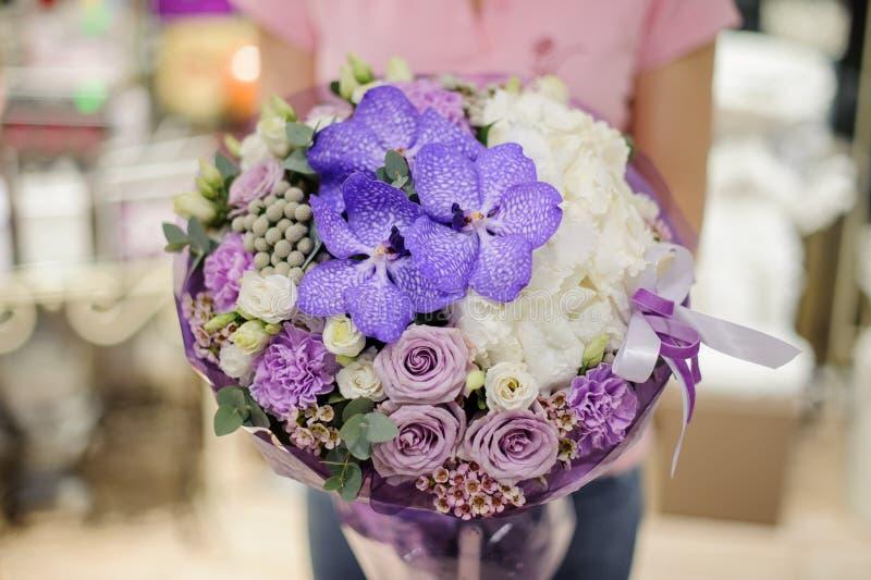 Bloemist die tedere bloemsamenstelling in blauwe, witte en purpere tonen houden die uit rozen en andere mooie bloemen bestaan stock foto