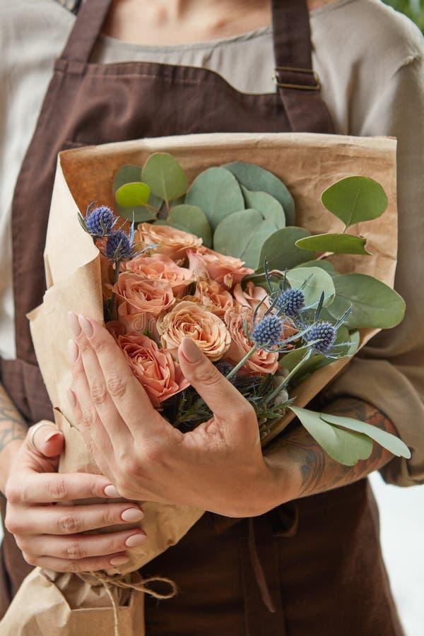 Bloemist in een bruine schort met een boeket van koraalrozen Het meisje houdt bloemen in haar handen De mening van de close-up De royalty-vrije stock afbeeldingen