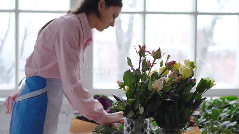 Bloemist op het werk: jonge vrouw die modern boeket van verschillende bloemen maken royalty-vrije stock fotografie