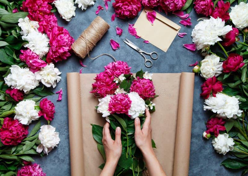 Bloemist op het werk: mooie vrouw die de zomerboeket van pioenen op een werkende grijze lijst maken Kraftpapier-document, schaar, stock foto's