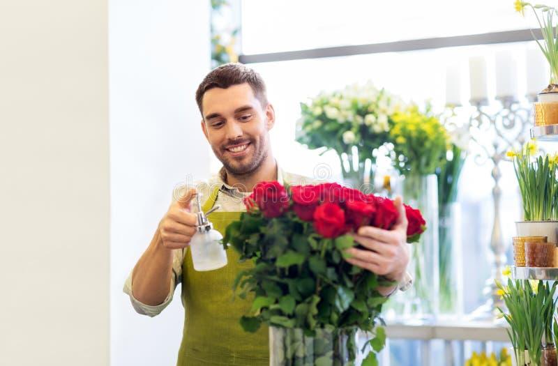 Bloemist of verkoper die rode rozen plaatsen bij bloemwinkel royalty-vrije stock foto