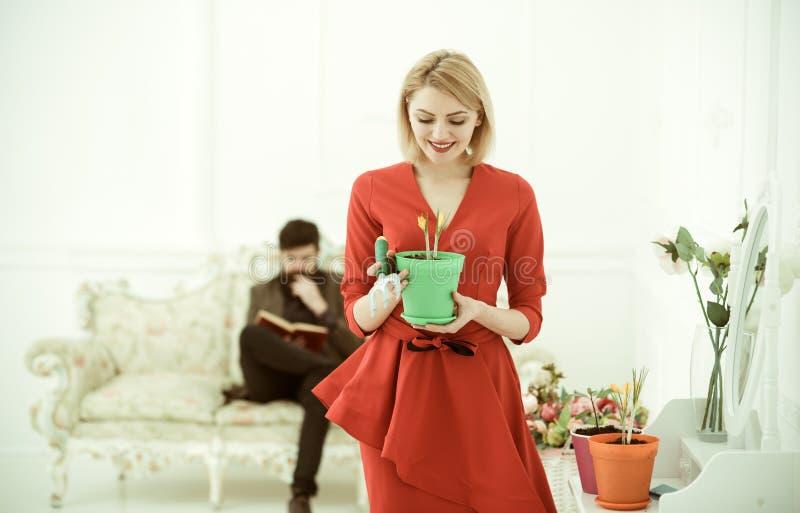 Bloemistconcept De glimlach van de bloemistvrouw met de lentebloem terwijl man lezingsboek op bank Huisbloemist op het werk flori stock foto
