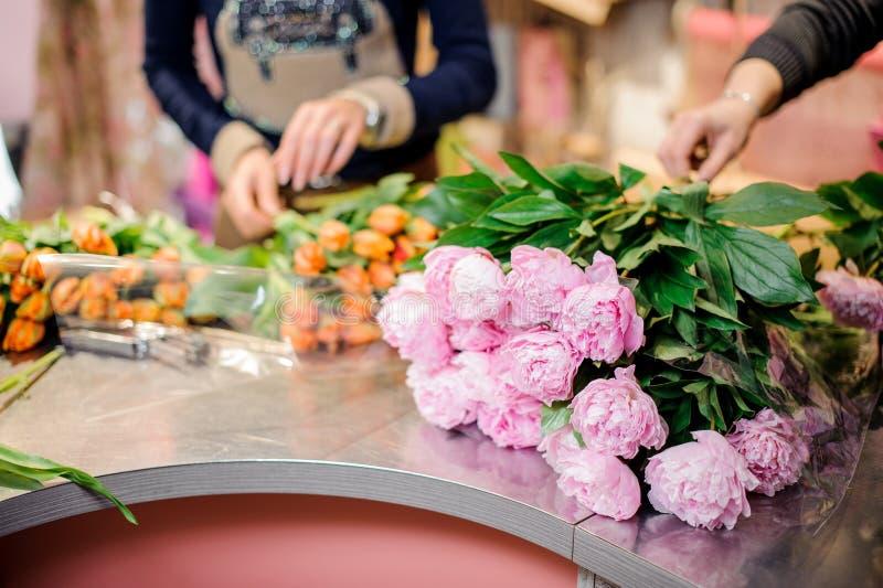Bloemisten die boeketten van roze kleurenpioenen en oranje tulp maken stock foto
