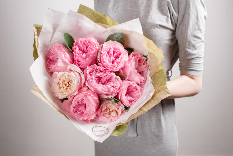 Bloemistmeisje met pioenbloemen of roze tuinrozen Het jonge boeket van de vrouwenbloem voor de dag van de verjaardagsmoeder royalty-vrije stock fotografie