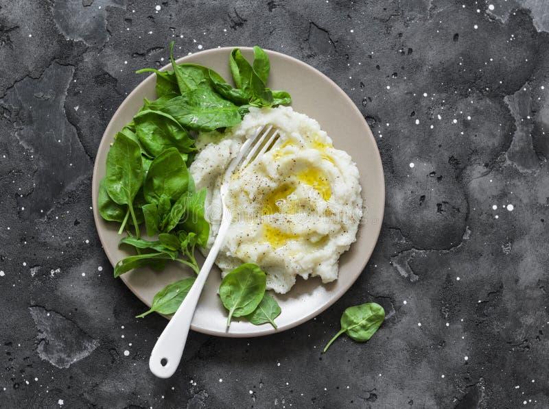 Bloemkool met spinazie wordt fijngestampt die De heerlijke vegetarische lunch of versiert op een donkere achtergrond, hoogste men stock foto's