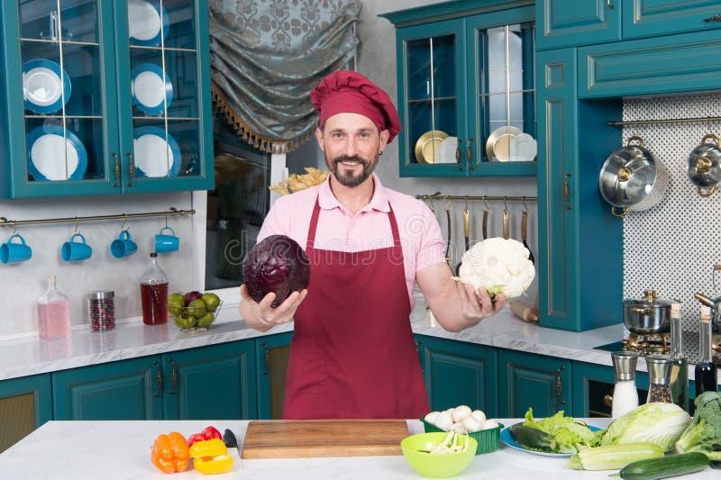 Bloemkool versus rode kool door chef-kok te kiezen De mens toont grote Bloemkool en rode kool alvorens en snijdend voor salade vo royalty-vrije stock foto