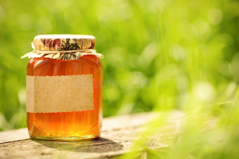 Bloemrijke honing met leeg etiket in glaskruik stock fotografie