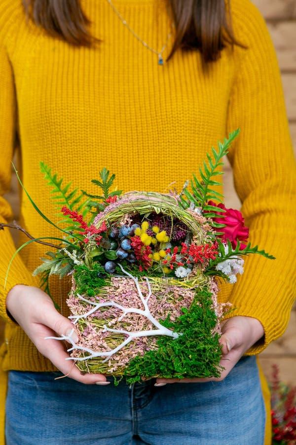 Bloemsamenstelling in handen van bloemist in het stadium van voltooiing royalty-vrije stock afbeelding