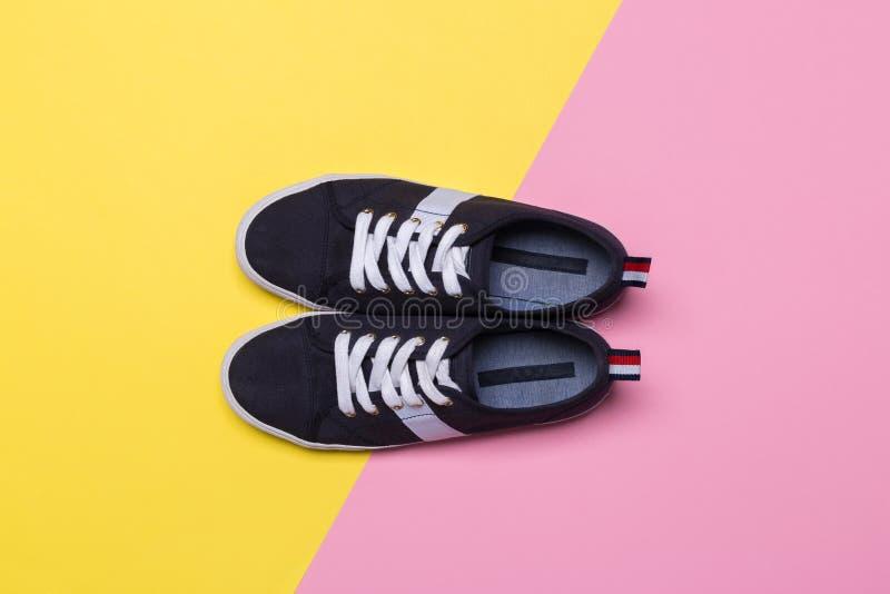 Πάνινα παπούτσια στο ρόδινο και κίτρινο υπόβαθρο Μόδα blog ή έννοια περιοδικών στοκ εικόνα με δικαίωμα ελεύθερης χρήσης