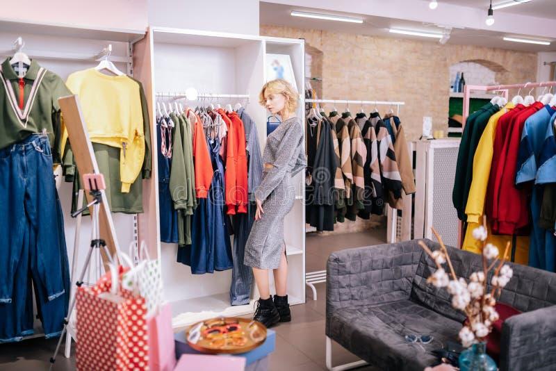 Blog blond de mode de pelliculage de styliste dans la salle d'exposition spacieuse images libres de droits