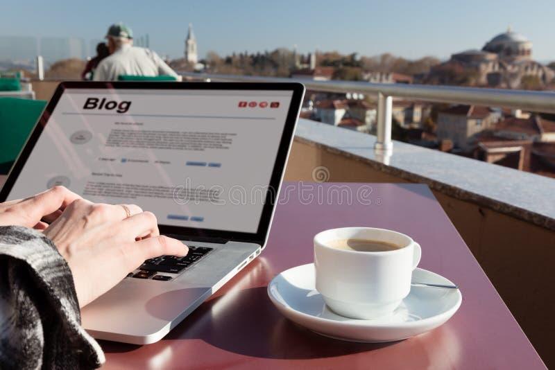 Blog d'écriture de personne sur l'ordinateur portable au café de dessus de toit photo libre de droits