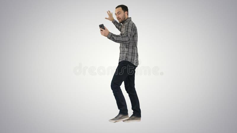 Blog de enregistrement de vlog d'homme barbu bel avec le smartphone tout en marchant sur le fond de gradient images libres de droits