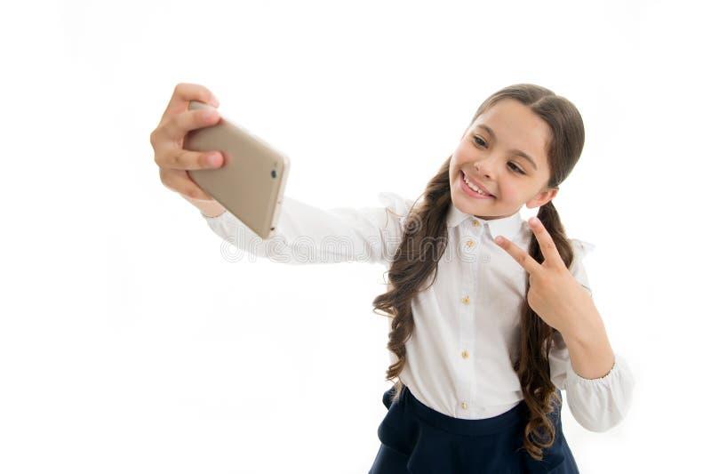 Blog la pequeña muchacha hace la foto para su blog personal comparta su blog en línea blog de la niñez del niño aislado encendido imagen de archivo libre de regalías