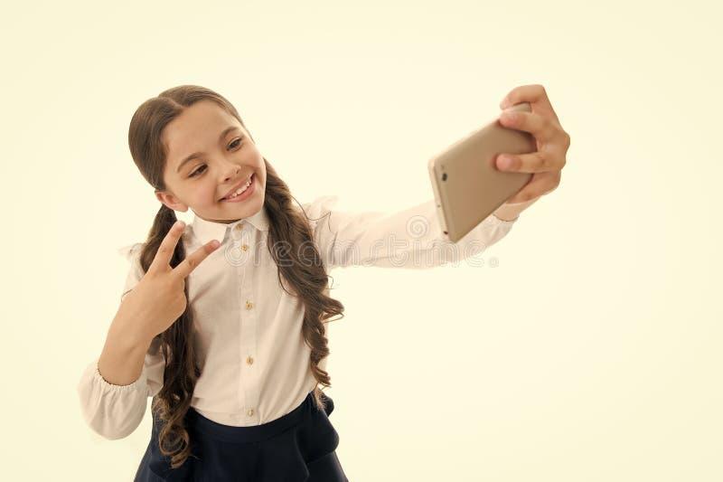 Blog la pequeña muchacha hace la foto para su blog personal comparta su blog en línea blog de la niñez del niño aislado encendido fotografía de archivo libre de regalías