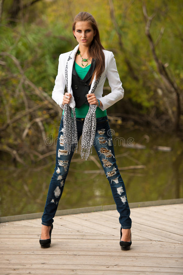 Blog style beautiful brunette woman in fashionable dress posing royalty free stock photography
