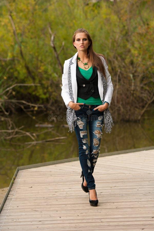 Blog style beautiful brunette woman in fashionable dress posing stock image