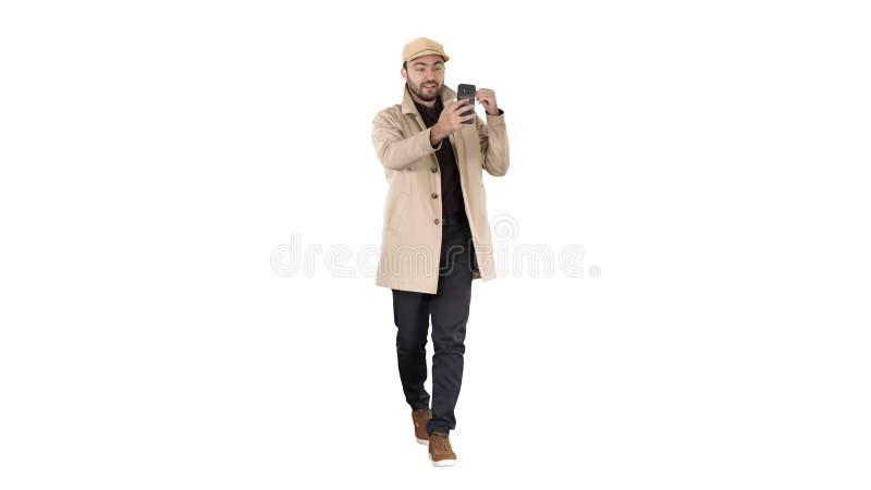 Blog video di registrazione dell'uomo di stile di modo di autunno che cammina sul fondo bianco fotografie stock libere da diritti