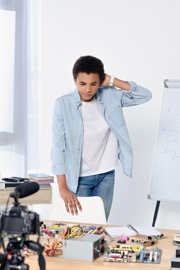 blog visuel d'afro-américain de tir songeur d'adolescent et regarder la table photos stock
