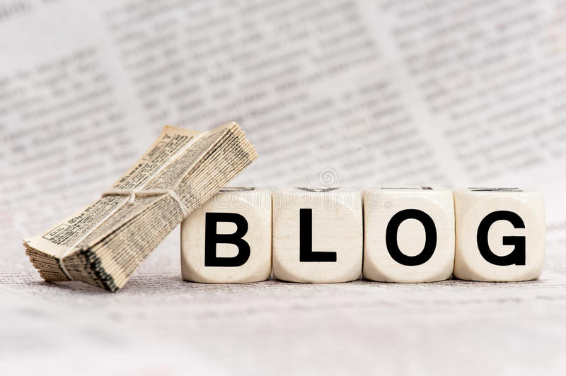 Blog. Woodn dice depicting the letters BLOG, with a stack of newspapers leaning on a dice
