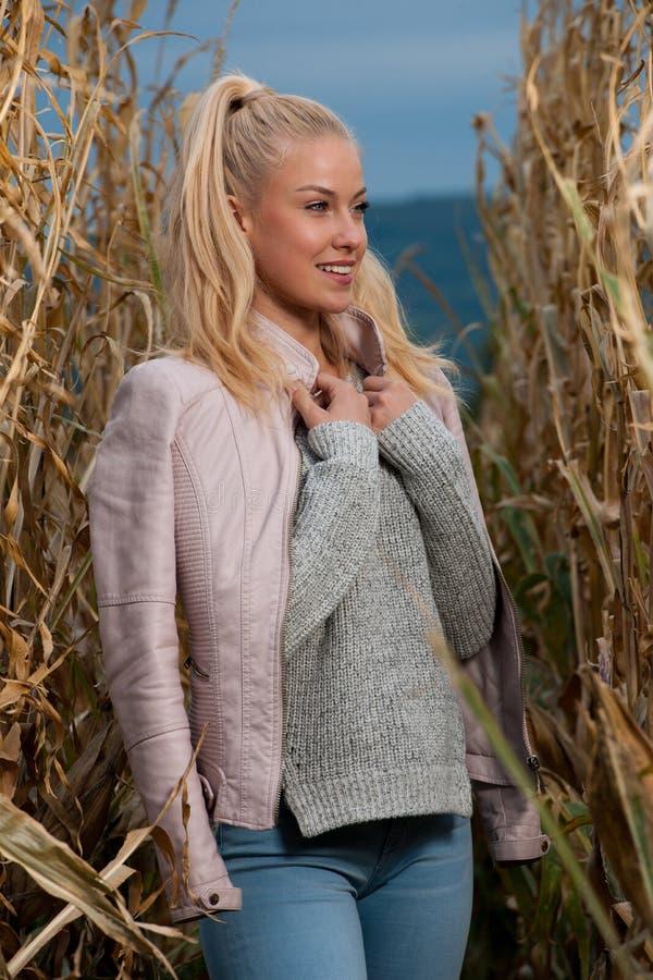 Blogart-Modefoto der netten blonden Frau auf Maisfeld im Spätherbst stockfoto