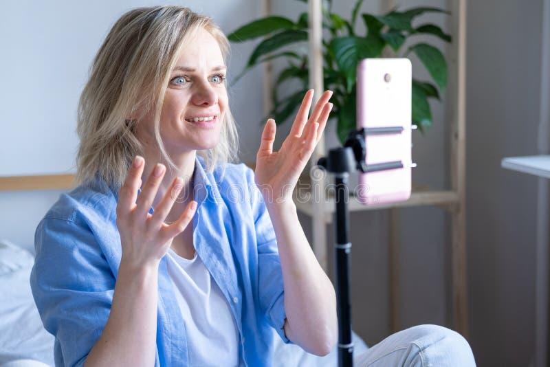Bloger kobiecy rozmawiający ze zwolennikami, transmisje na żywo, szukający smartfona siedzącego na łóżku Nawiązywanie połączenia  obraz royalty free