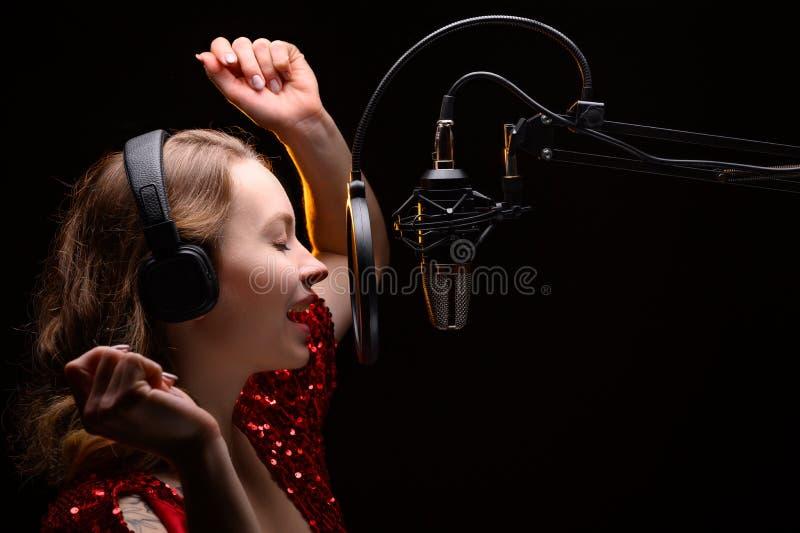 Bloggare för sångare eller radiovärddatorer som arbetar i en professionell studio Spela in ett ljudspår, album, arbeta med en eti arkivbilder