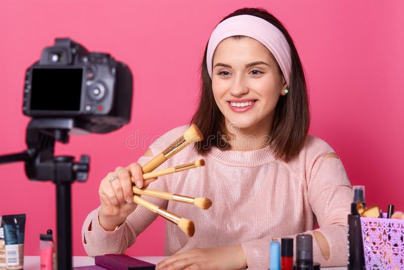 Bloggende, moderne Technologie und Leutekonzept Glücklicher lächelnder Frauenschönheit Videoblogger hält Bürsten für Make-up beim stockbild