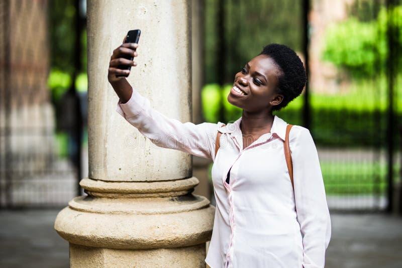 Blogger afroamericano atractivo de la mujer joven vestido en el equipo casual de moda que hace el selfie vía smartphone para comp imágenes de archivo libres de regalías