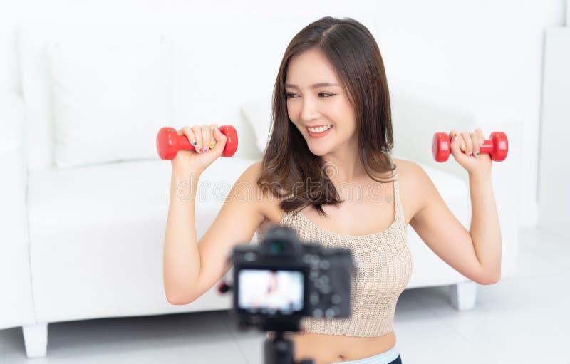 Blogger asiático hermoso deportivo de la mujer que registra un vídeo que ejercita en casa para permanecer apto fotos de archivo
