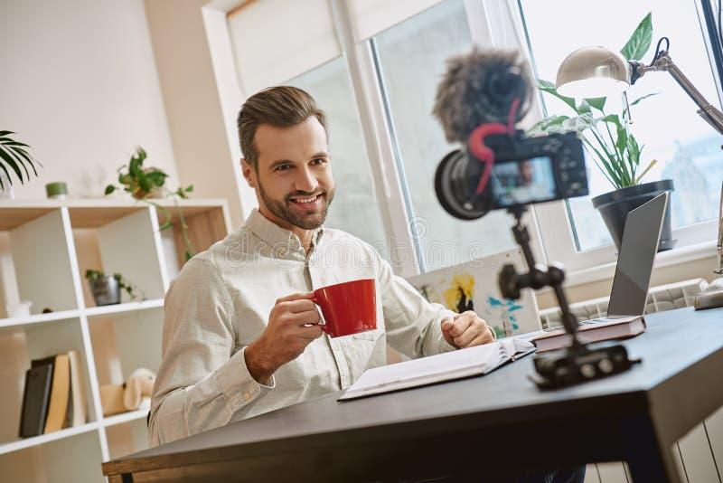 Blogger bem sucedido Retrato do blogger masculino de sorriso que bebe um chá ao fazer um vídeo novo em casa imagens de stock royalty free