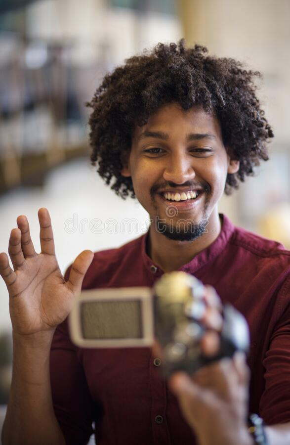 He is a blogger. Business man using camera in office royalty free stock image