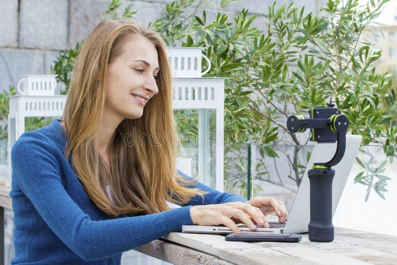 Blogger bonito de la moda que hace informe de la corriente con el ordenador portátil fotografía de archivo