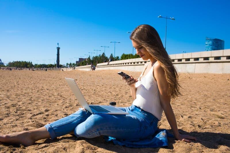 Blogger causant sur le téléphone portable tout en se reposant dehors photographie stock libre de droits