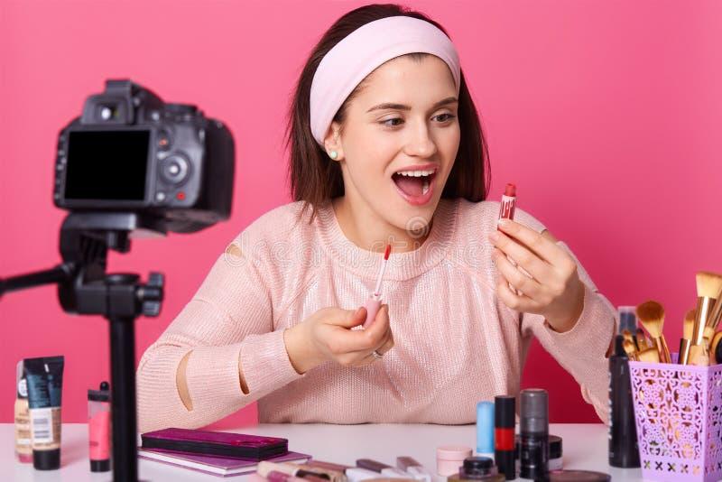 Blogger da beleza com vídeo novo dos shooots da câmera para seu vlog A fêmea moreno anuncia produtos dos cosméticos Posses da jov imagem de stock