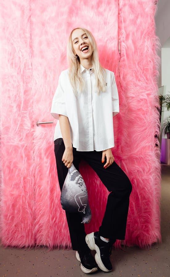 Blogger da moça vestido na camisa branca à moda e em poses pretas da calças com com um brinquedo macio na forma de um pombo imagem de stock royalty free
