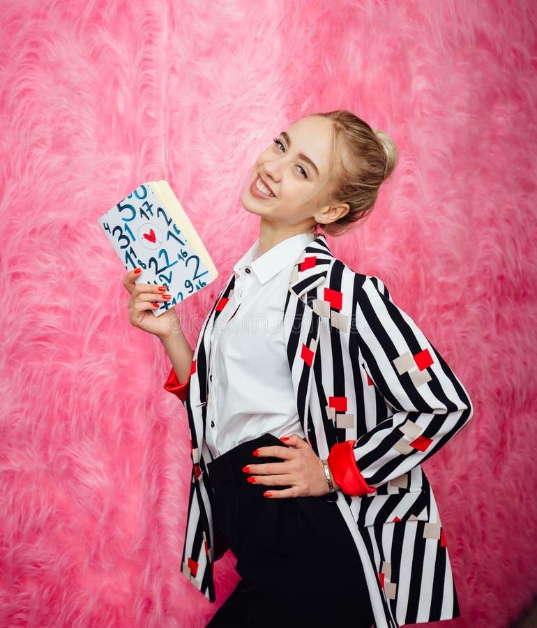 Blogger da mo?a da forma vestido na camisa listrada ? moda e em poses vermelhas da cal?as no fundo da parede cor-de-rosa da pele fotos de stock