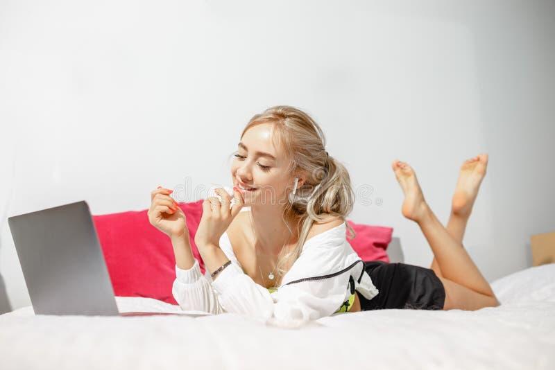Blogger de jeune fille habillé dans des vêtements à la mode se trouvant sur le lit et fonctionnant à l'ordinateur portable dans l image stock