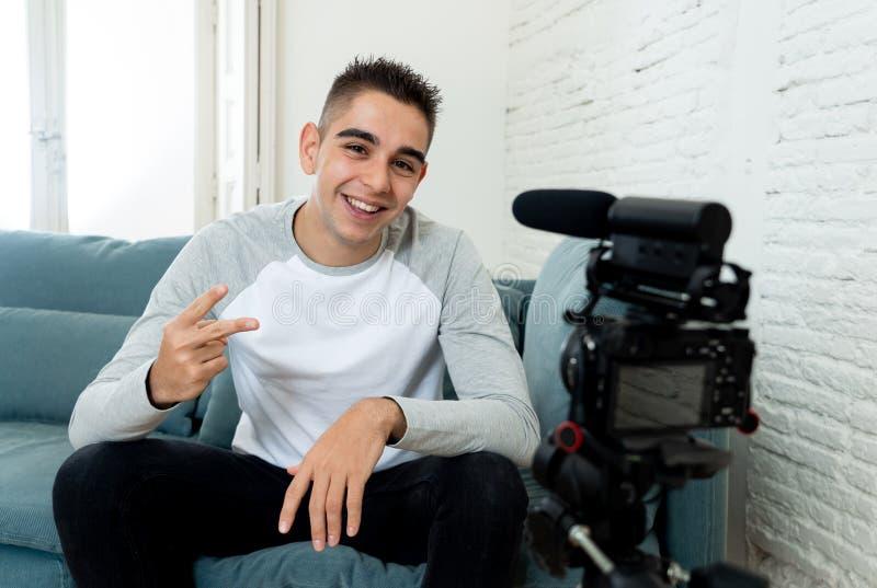 Blogger de jeune homme en ses années '20 enregistrant une vidéo sur la caméra pour des disciples sur l'Internet photographie stock