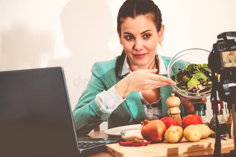 Blogger de la comida o vídeo de registración del influencer sobre la comida sana usando cámara y el ordenador portátil fotos de archivo libres de regalías