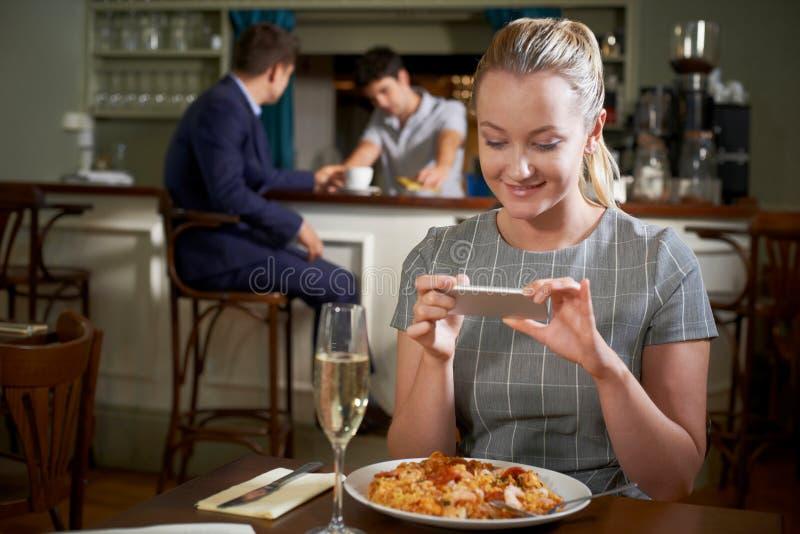 Blogger de la comida que toma la imagen de la comida del restaurante en el teléfono móvil imagenes de archivo