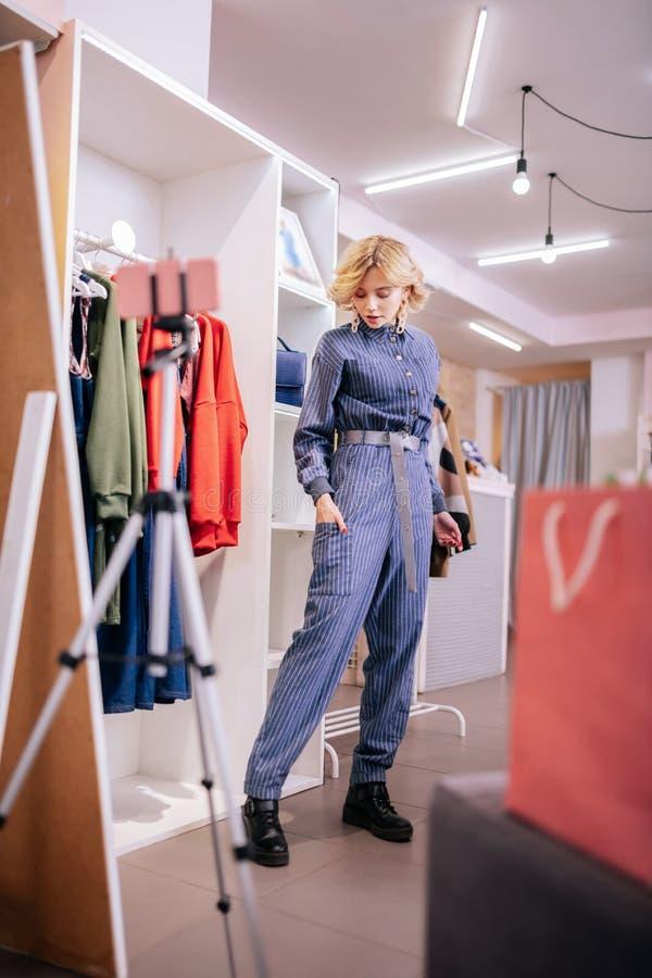 Blogger de mode avec les cheveux blonds courts posant et filmant le blog photo libre de droits