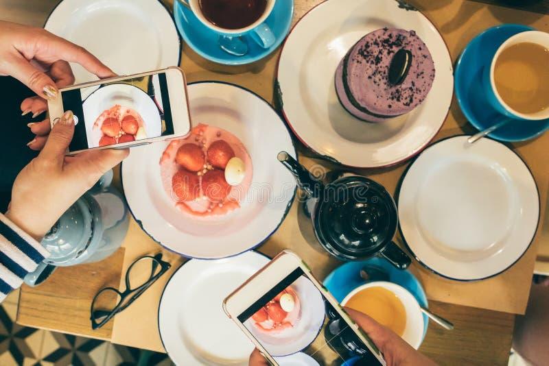 Blogger dei fotografi dell'alimento che prendono foto dei dolci nella tavola del caffè Vista superiore Pranzo degli amici, divert immagini stock libere da diritti
