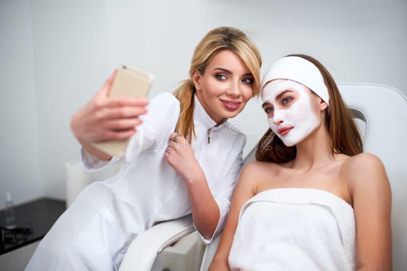 Blogger del cosmetólogo que hace el selfie con el cliente después de aplicar la máscara facial para la piel sana Mujeres atractiv imagen de archivo