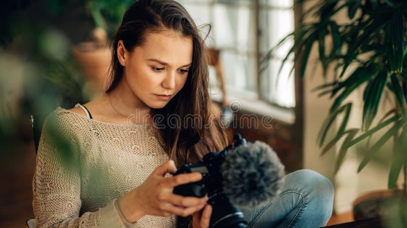 Blogger della donna che esamina la sua macchina fotografica fotografia stock